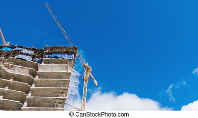 Cranes at a skyscraper construction and blue sky with cloud