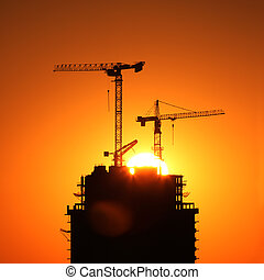Cranes at sunrise - Industrial construction cranes and...