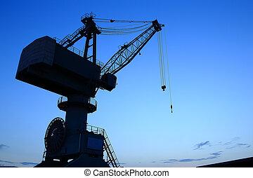 Cranes in dockyard at sunset