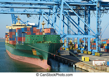 Cranes load containers on large transport ship - Cranes load...