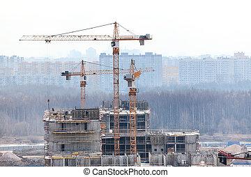 Cranes on construction site build high-rise building