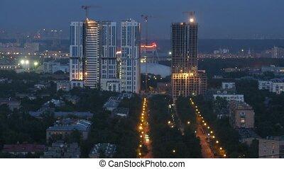 Cranes operate above apartment building construction site