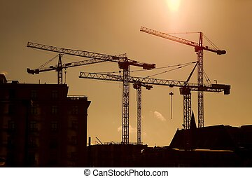 Cranes - Tower crane silhouettes at a construction site