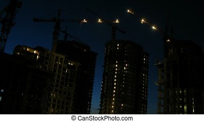 Cranes work on construction site after sunset, time lapse
