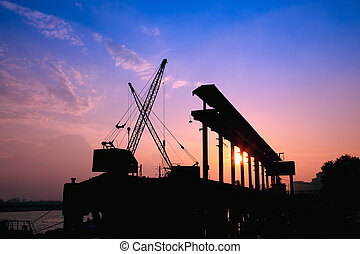 Cranes working at sunset