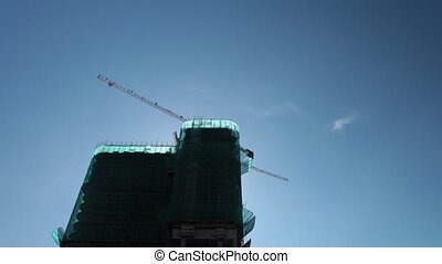 Cranes Working On High Rise Construction Site - Cranes in...