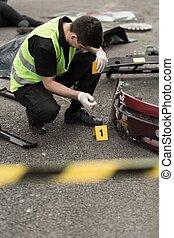 Crash site investigation - Policeman is numbering evidences ...