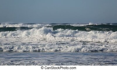 Crashing waves over against blue sky along Pacific Ocean in...