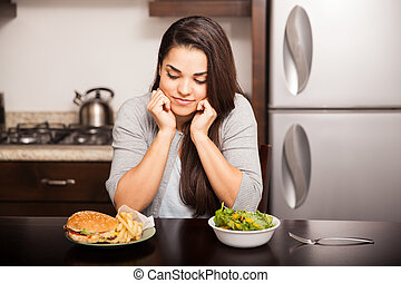 Beautiful young woman thinking on choosing a burger over a salad for dinner at home