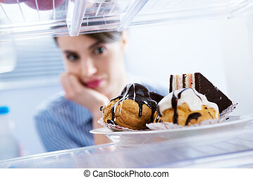 Craving sweet food - Young hungry woman in front of ...