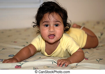 Handsome Indian kid learning to crawl on the bed