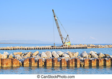 Crawler Crane at work on a river and sea shore