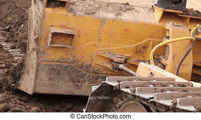 Close up view on bulldozer's undercarriage during pushing ground at construction site. Photo - JPEG video codec