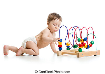 Crawling baby in a diaper plays with educational toy isolated on white