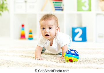 crawling funny baby boy indoors at nursery