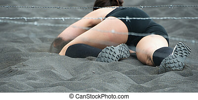 Crawling,passing under a barbed wire obstacles during...