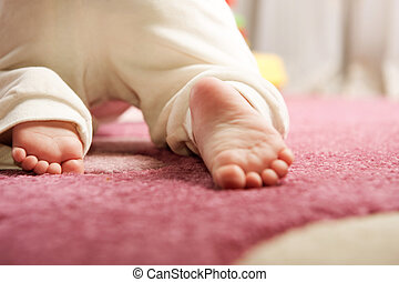Crawling - Little baby crawling on the pink carpet. Rear...