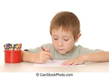 Young Boy Coloring A Sheet Of Paper With Crayon