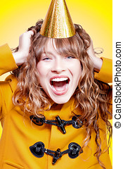 Crazy and overjoyed party girl in a gold party hat laughing...