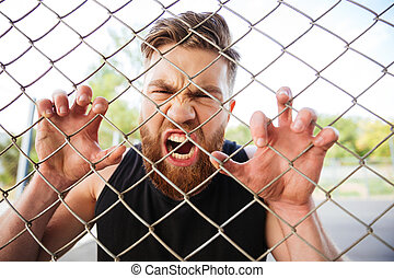 Crazy bearded man shouting with his hands on metal fence