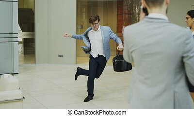 Crazy businessman dancing with briefcase in modern lobby...