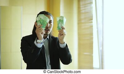 Crazy businessman dancing with money and looking at himself in the mirror