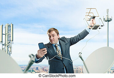 Crazy businessman with antenna and cell phone trying to ...