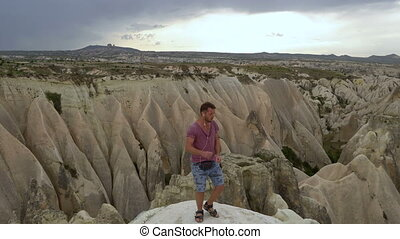 Crazy Caucasian Male Dancing with headphones in his ears on the Top of Mountain in Cappadocia, Turkey.