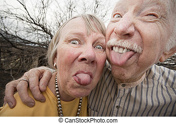 Crazy Couple Sticking Out Tongues - Closeup portrait of...