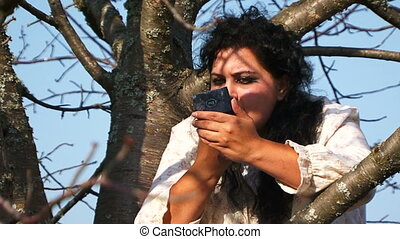 Crazy Dark-Haired Woman In Long White Nightie Putting On Lipstick Sitting On Tree