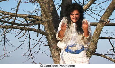 Crazy Dark-Haired Woman In Long White Nightie Throwing Pillow Feathers Around Sitting On Tree