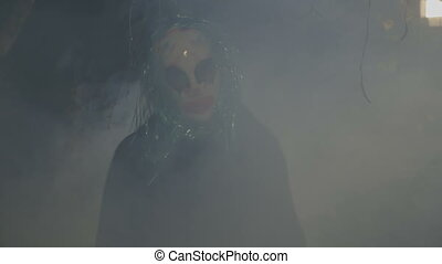 Crazy evil halloween clown coming up from a foggy wood and...