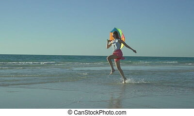 Crazy funny woman in pink skirt with sunglasses is running and jumping on the beach. Vacation has come. Happy girl jumps with rainbow umbrella, enjoys her summer vacation. Slow motion