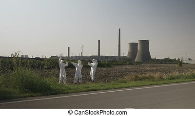 Crazy hazmat team of workers dancing near a nuclear power plant funny concept of ecology