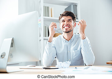 Crazy irritated businessman holding crumpled paper and working on workplace