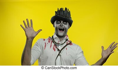 Crazy man with horrible Halloween skeleton makeup in costume with top-hat appears from bottom side, looking at camera, trying to scare. Horror theme. Yellow background. 6k downscale. Copy space