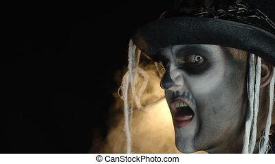 Side view of crazy man with horrible Halloween skeleton makeup in costume with top-hat making faces, showing tongue, trying to scare. Horror theme. Day of The Dead. Black background. 6k downscale