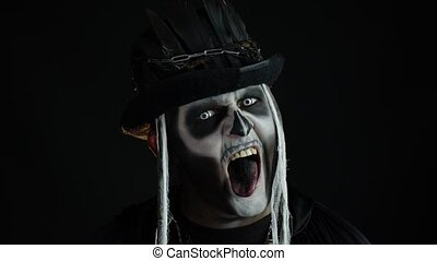 Crazy man with horrible Halloween skeleton makeup in costume with top-hat making faces, showing tongue, trying to scare. Horror theme. Day of The Dead. Isolated on black background. 6k downscale