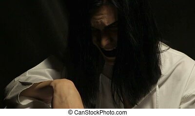 Crazy man with long hair on black background