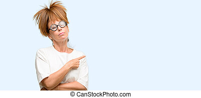 Crazy middle age woman wearing silly glasses pointing away side with finger