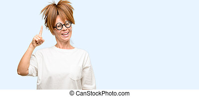 Crazy middle age woman wearing silly glasses raising finger, the number one