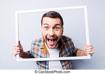 Crazy picture. Handsome young man in shirt holding picture frame in front of his face and smiling while standing against grey background