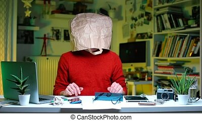 Crazy sick man sitting at a table in the office. On his head is a paper bag.