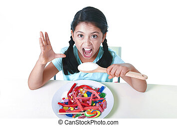 crazy spastic child eating dish full of candy holding sugar spoon in dangerous diet and sweet nutrition abuse