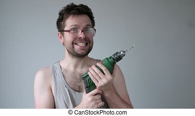 Crazy young man in big glasses going mad doing repair holding drill in hands.