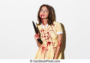 Crazy zombie woman in dress holding knife