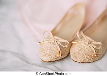 Cream bride shoes on green on a white background
