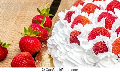 Cream cake with strawberries on wooden table