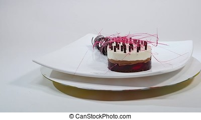 Cream cake with three layers on a plate. Cream cake with three layers, decorated with chocolate crumbs and chocolate straw