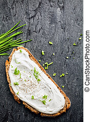 Overhead view of delicious cream cheese and chopped chives on a slice of rye or wholewheat bread on a dark textured surface with copyspace